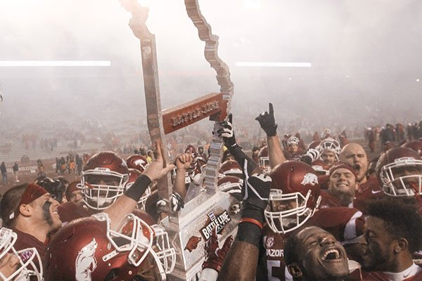 Arkansas players lift the Battle Line Trophy after beating Missouri 28-3 on Friday, Nov. 27, 2015, at Razorback Stadium in Fayetteville.
