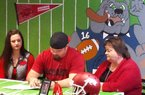 Star City defensive lineman Austin Capps is joined by his sister Mary Katherine and his mother Thea on Wednesday as he signs his National Letter of Intent with the University of Arkansas.