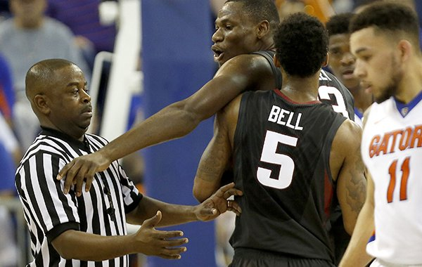 Arkansas guard Anthlon Bell (5) holds back forward Moses Kingsley (33) after Kingsley was called for a technical foul against Florida during the second half of an NCAA college basketball game at the O'Connell Center on Wednesday, Feb. 3, 2016 in Gainesville, Fla. Florida defeated Arkansas 87-83. (Matt Stamey/The Gainesville Sun via AP)