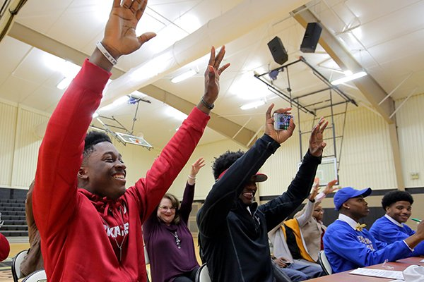 Pulaski Robinson's TJ Hammonds, calls the hogs with the crowd during a signing ceremony Wednesday at the Little Rock school. At right is classmate Tonda Bullock, who signed with Henderson State.