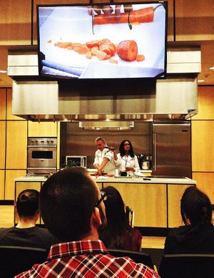 Members of the UAMS Integrative Medicine Interest Group watch as Chef Philippe Ducrot shows them how not to chop their fingers off while Dr. Meenakshi Budhraja holds the mic.