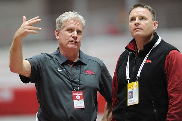 Arkansas track coach Chris Bucknam, left, talks with UA facilities director Scott Sargent during a meet Friday, Jan. 15, 2016, at Randal Tyson Track Center in Fayetteville.