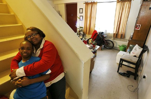 debra-aldridge-sits-with-her-grandson-mario-hendricks-at-her-home-on-chicagos-south-side