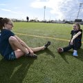 Bentonville High Junior Katie Andrews (left) stretches and visits Wednesday with Emmy Schaller who i...