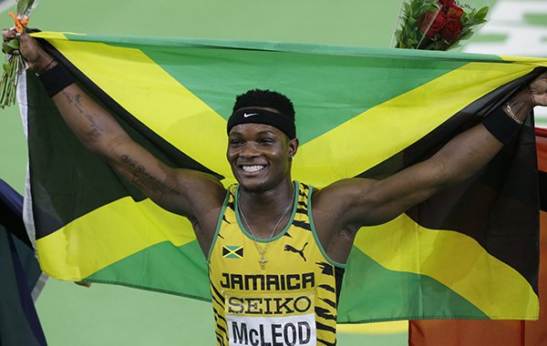 Jamaica's Omar McLeod holds a flag after he won the men's 60-meter hurdles final during the World Indoor Athletics Championships, Sunday, March 20, 2016, in Portland, Ore. (AP Photo/Rick Bowmer)