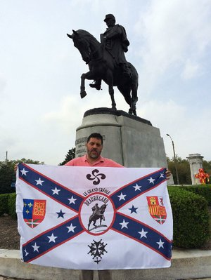 Michel-Antoine Goitia-Nicolas stands next to a statue of P.G.T. Beauregard earlier this month while displaying a flag associated with the Confederate general.