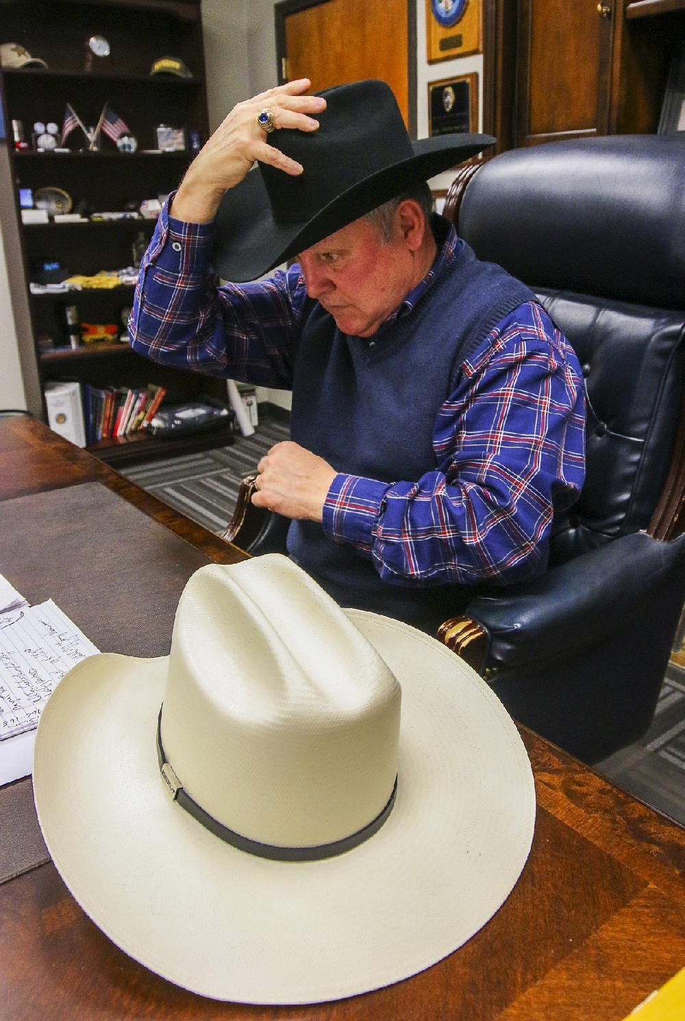 Pulaski County Sheriff Doc Holladay puts on his county-issued  155 Stetson  in his office Thursday. On his desk is a Resistol hat. 8bf32a9db73d