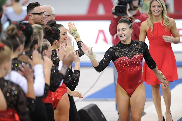 Arkansas' Stephanie Canizaro celebrates Friday, March 11, 2016, with teammates after competing in the floor rotation during the 11th-ranked Razorbacks' meet with Utah State in Barnhill Arena in Fayetteville.