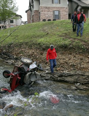 Workers with Land Design landscaping company remove a lawn mower from a creek Friday morning at Stonebridge Apartments in west Little Rock after a co-worker's accidental death.