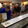 Ken Farmer, left, Bella Vista police chief, gazes Sunday at an exhibit in the Bella Vista Historical...