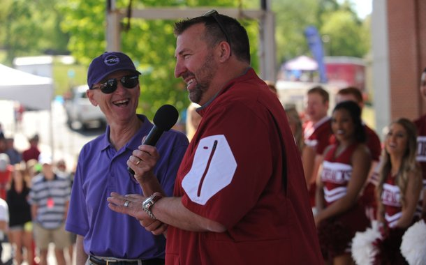 NWA Democrat-Gazette/ANDY SHUPE University of Arkansas football coach Bret Bielema (center) laughs Saturday as he speaks to the crowd alongside Rick Schaeffer during Razorfest ahead of the University of Arkansas spring football game at Razorback Stadium in Fayetteville. The event drew 40,000 people in 2015 and about 8,700 pounds of food was collected.