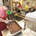 Deanna Allen, kitchen assistant at the Fayetteville Senior Activity and Wellness Center, slices a pa...