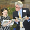 Lena Hart, member of Temple Shalom of Northwest Arkansas, is helped by Daniel Levine as she reads th...