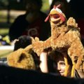 Killian Ward peeks from under his puppet during an Art Experience children's puppet workshop.