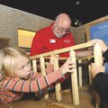 Jewel Conley builds the frame of a house at the Rogers Historical Museum.