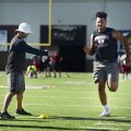 Brian Early, left, an assistant coach with Arkansas State, times Isaiah Nichols of Springdale in the...