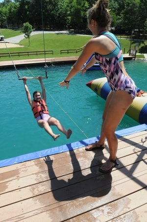 Halle Hill (left), a camper at Camp War Eagle, is set Wednesday to take a pool plunge from a swing with help from Jordan Maass, a counselor at the camp near Rogers.