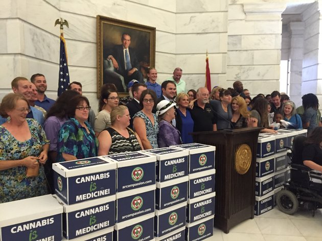 supporters-of-the-arkansas-medical-cannabis-act-stand-with-boxes-of-signatures-backing-their-proposal-at-a-news-conference-monday-june-20-2016