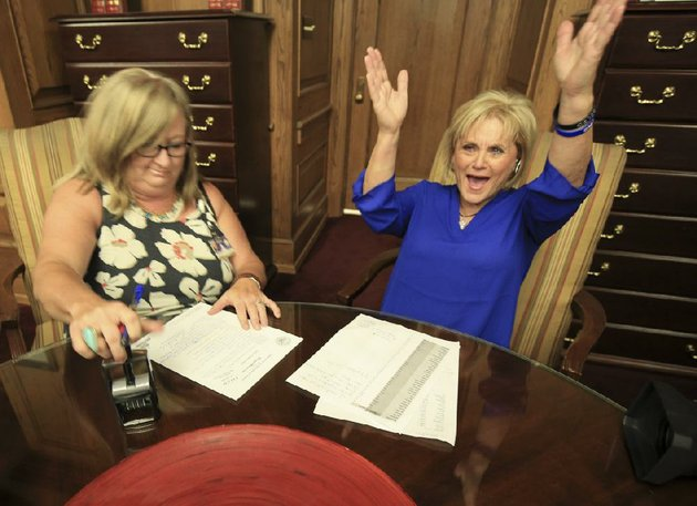 arkansans-for-compassionate-care-campaign-director-melissa-fults-right-celebrates-as-leslie-bellamy-of-the-secretary-of-states-office-stamps-paperwork-for-petitions-that-fults-group-delivered-in-june-in-hopes-of-getting-a-medical-marijuana-initiative-on-the-ballot