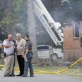 Emergency personnel collect evidence Friday at the intersection of Brown Street and Neal Street. Aut...
