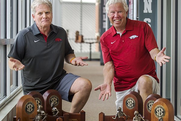 Arkansas track coaches Chris Bucknam, left, and Lance Harter pose with their SEC championship trophies won during the 2015-16 year.