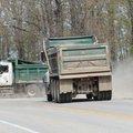 Dump trucks with the Washington County Road Department exit a gravel road onto Arkansas 16 Thursday,...