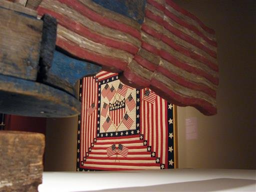 in-this-june-30-2016-photo-a-patriotic-quilt-is-framed-by-a-flag-trailing-uncle-sam-on-a-bicycle-whirligig-at-the-exhibit-american-made-treasures-from-the-american-folk-art-museum-at-the-crystal-bridges-museum-of-american-art-in-bentonville
