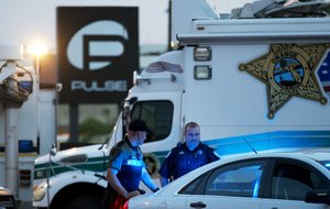 FILE - In this June 17, 2016 file photo, law enforcement officials stand outside the Pulse nightclub following Sunday's mass shooting, in Orlando, Fla. More police departments are exploring technology that would allow 911 emergency dispatchers to receive text messages from people who need help. When gunshots rang out at the Pulse nightclub in Orlando last month, patrons hid from the gunman and frantically texted relatives to call 911 because Orlando doesn't have 911 texting. (AP Photo/David Goldman, File)