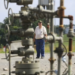 "Verlon Abram stands near one of the many natural-gas wells on his property in Cleburne County. Though his royalty checks are shrinking, ""the gas companies were good to me,"" Abram says."
