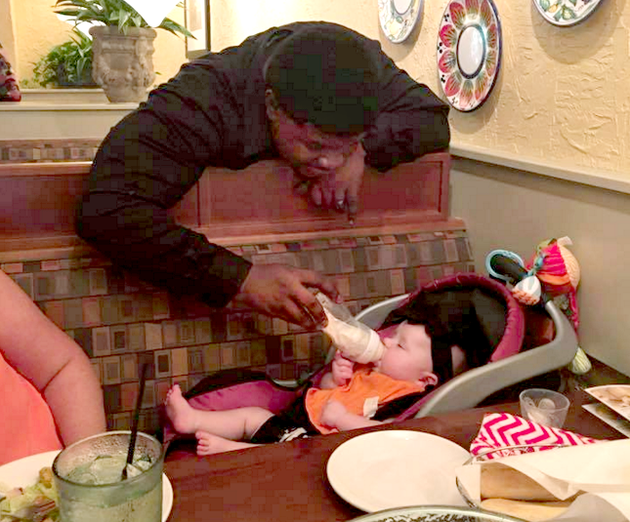 the-waiter-for-dallas-french-and-her-family-who-a-coworker-identified-as-robert-davis-feeds-frenchs-daughter-at-olive-garden-while-the-family-took-a-break-to-eat-on-thursday-the-photo-was-picked-up-by-the-love-what-matters-facebook-page-and-has-been-shared-more-than-6500-times