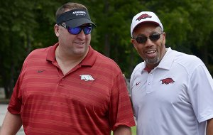 Bret Bielema (left), Arkansas head football coach, and Vernon Hargreaves, linebackers coach, talk on Friday July 29, 2016 during the NWA Razorback Club's 15th Annual Celebrity Golf Tournament at the Kingswood and Berksdale golf complex in Bella Vista.