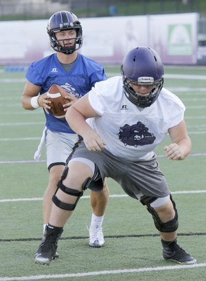 Fayetteville High School quarterback Taylor Powell takes a snap under center from Max Thurman Monday, August 1, 2016, during practice at Harmon Stadium in Fayetteville. The Fayetteville High School Football team is now being coached by first year head coach Bill Blankenship.