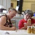 Carol Funk (left) writes notes after reviewing an entry with Rosa Thomas in the food preservation co...