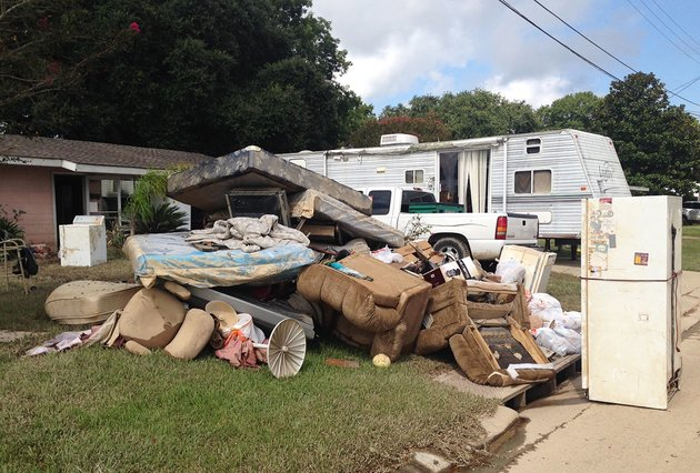a-growing-pile-of-debris-sits-outside-the-flood-ravaged-home-of-carolyn-and-james-smith-in-denham-springs-la-on-wednesday-aug-17-2016-smith-says-she-and-four-other-adults-will-live-for-the-time-being-in-the-travel-trailer-that-one-of-her-sons-towed-to-the-driveway-after-weekend-flooding-inundated-the-area-ap-photokevin-mcgill
