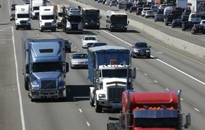 Tractor-trailers roll with the traffic on Interstate 5 near Fife, Wash. The American Trucking Associations backs a proposal to limit the speed of heavy-duty vehicles.