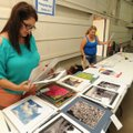 Stacey Watkins (left) of Springdale and Chal Sims of Lowell sort through submissions Saturday while ...