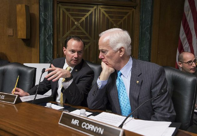 sen-mike-lee-left-r-utah-confers-with-sen-john-cornyn-r-texas-on-capitol-hill-in-washington-in-this-march-16-photo