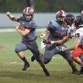 Springdale High's running back Garrett Vaughan (left) finds a hole in the Russellville defense Frida...