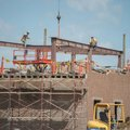 Contractors for Milestone Construction Co. erect steel beams Monday at the former Tyson Foods headqu...