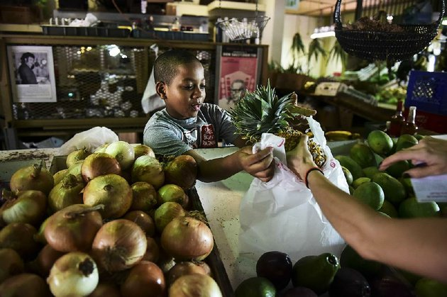 yoniel-santana-works-at-his-grandmothers-produce-stand-last-week-at-la-placita-de-santurce-farmers-market-which-sells-mostly-locally-grown-produce-in-san-juan-puerto-rico