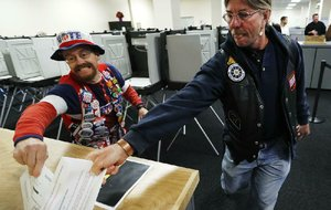 Iowans John Olsen (left) and Mark Cooper compete Thursday to be the first to drop a ballot into the box in Des Moines on the first day of early voting in the state.