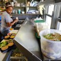 A bucket sits on the counter for unused food items Friday as Sharrita Turner, line cook, prepares fo...