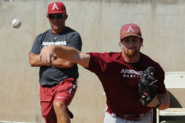 Arkansas' Dominic Taccolini warms up Friday, Sept. 9, 2016, as pitching coach Wes Johnson observes during practice at Baum Stadium in Fayetteville.