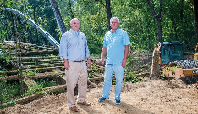 jack-bell-left-chief-of-staff-for-the-city-of-conway-and-steve-ibbotson-director-of-the-conway-parks-and-recreation-department-stand-at-the-foot-of-the-1874-springfield-des-arc-bridge-which-will-be-moved-to-beaverfork-lake-in-conway-work-is-underway-to-clear-the-road-and-make-a-gravel-pad-for-a-crane-to-sit-on-as-it-lifts-the-bridge-scheduled-for-the-first-of-november-so-it-can-be-restored-the-bridge-spans-cadron-creek-at-the-faulkner-conway-county-line