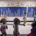 Students at Parson Hills Elementary School in Springdale walk by an attendance board Friday in a ha...