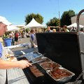 Russell Ellis grills bratwursts during last year's Rogers Octoberfest — now OktoBeerFest, with even ...