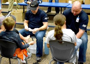 Photo by Mike Eckels Two volunteers from Walmart Distribution Center 6051 in Bentonville talked to a pair of students during the Samaritan's Feet distribution at Decatur Northside Elementary School Oct. 28. Walmart DC 6051 and Samaritan's Feet donated a new pair of socks and shoes to each student at the school.