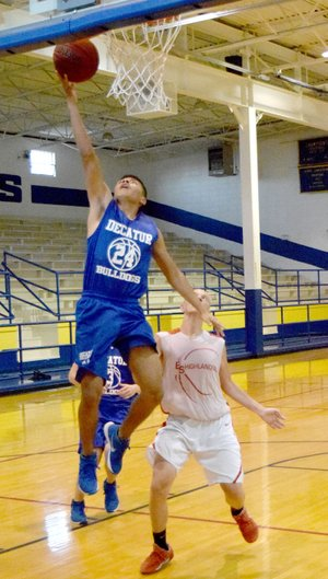 Photo by Mike Eckels Decatur's Marck Guadarrama (24) goes for a lay up against a Highlander player during the second game of the Decatur Summer Classic at Peterson Gym in Decatur June 14. Guadarrama is one of six seniors that are returning for their final season with the Bulldogs.