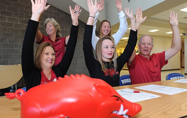 Rogers golfer Brooke Matthews (center) is joined by her mother, Gwen Mathews (clockwise from left); coach Brenda Alexander; sister, Brittany Matthews, 15; and father, Terry Matthews, as they call the Hogs Wednesday, Nov. 9, 2016, after Brooke Matthews signed a letter of intent to play golf for Arkansas during a signing ceremony at the school.