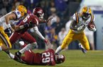 LSU running back Leonard Fournette (7) is tackled by Arkansas defensive back Jared Collins (29) and defensive back Rohan Gaines in the first half of an NCAA college football game in Baton Rouge, La., Saturday, Nov. 14, 2015. (AP Photo/Gerald Herbert)